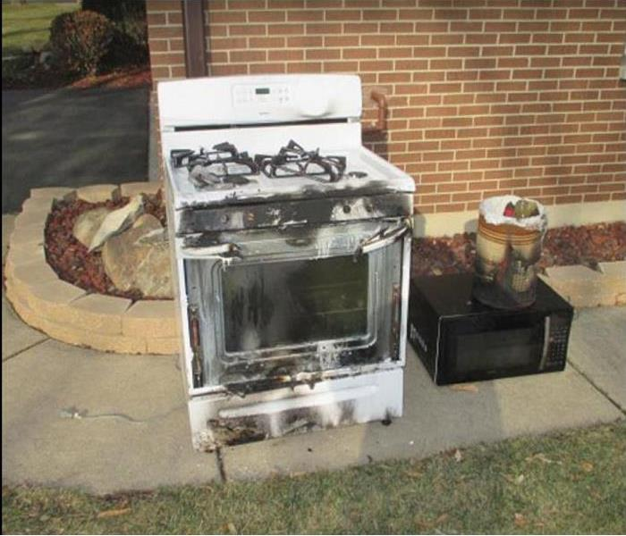 Fire damaged stove and microwave sitting outside on sidewalk