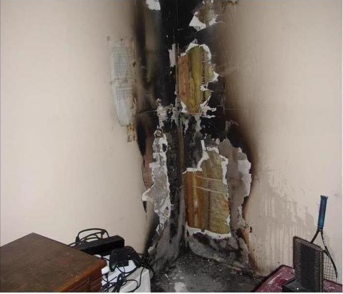 A corner in a bedroom wall that is covered from top to bottom in fire damage