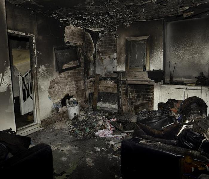 A living room with fire and soot damage.
