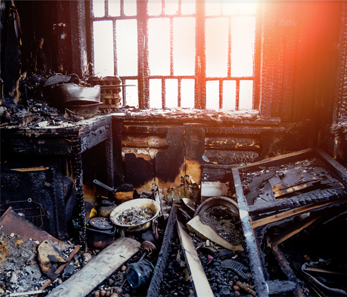 burned kitchen and remains of furniture in black soot